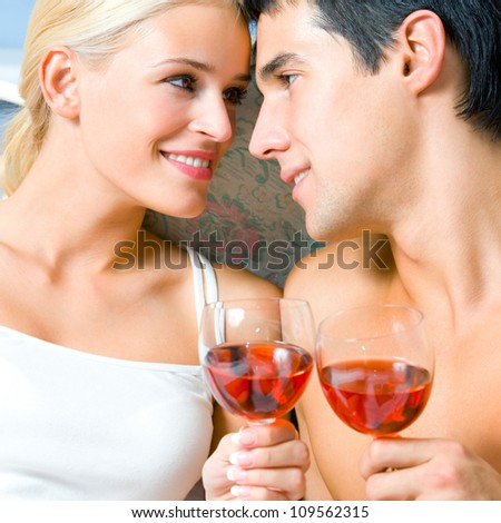 Portrait of cheerful smiling couple with glasses of red wine, indoors - stock photo