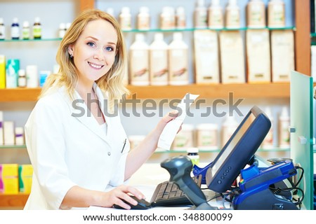 portrait of cheerful smiling female pharmacist working at the cash register in pharmacy drugstore - stock photo