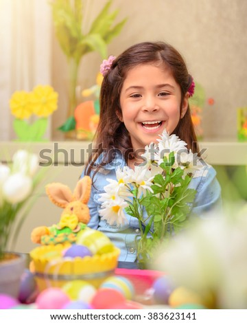 Portrait of cheerful smiling little girl sitting in the child's room with beautiful daisy flower bouquet, celebrating Easter holiday, happy spring season