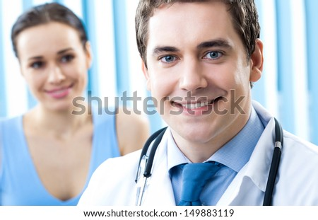 Portrait of cheerful smiling male doctor and female patient - stock photo
