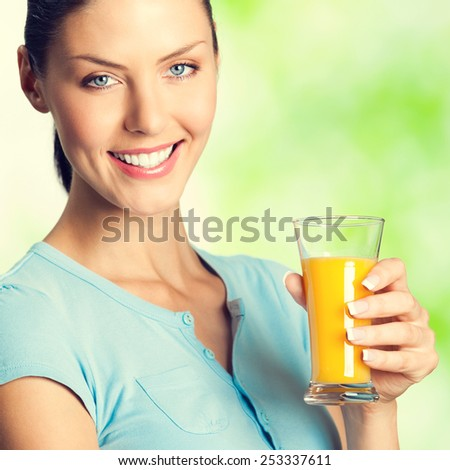 Portrait of cheerful smiling woman with glass of orange juice, outdoors - stock photo