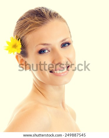 Portrait of cheerful smiling woman with yellow flower - stock photo