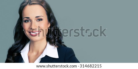 Portrait of cheerful smiling young businesswoman in black suit, with blank copyspace area for slogan or text - stock photo