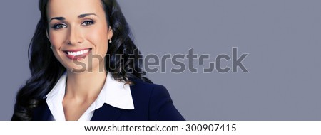 Portrait of cheerful smiling young businesswoman in black suit, with blank copyspace area for text or slogan, posing at studio, over violet background - stock photo