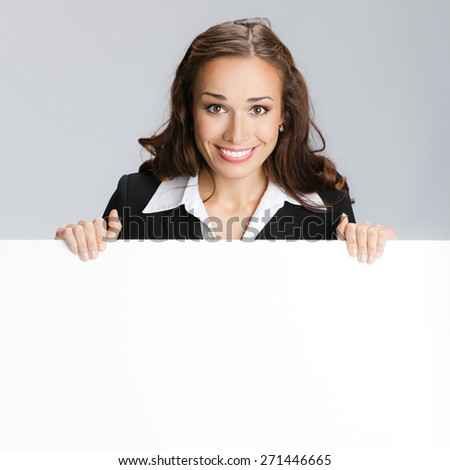 Portrait of cheerful smiling young businesswoman showing signboard with blank copyspace area for text or slogan - stock photo