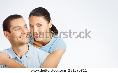Portrait of cheerful smiling young couple, with copyspace blank area for text or slogan, against grey background - stock photo