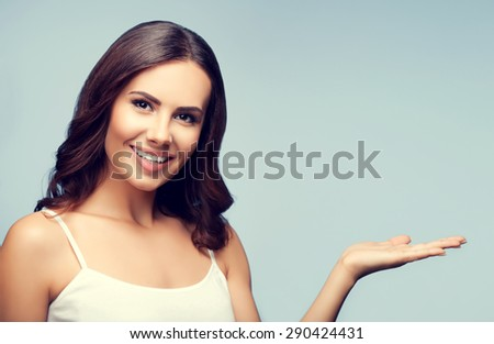 Portrait of cheerful smiling young woman in white casual clothing showing something or blank copyspace area for slogan or text message - stock photo