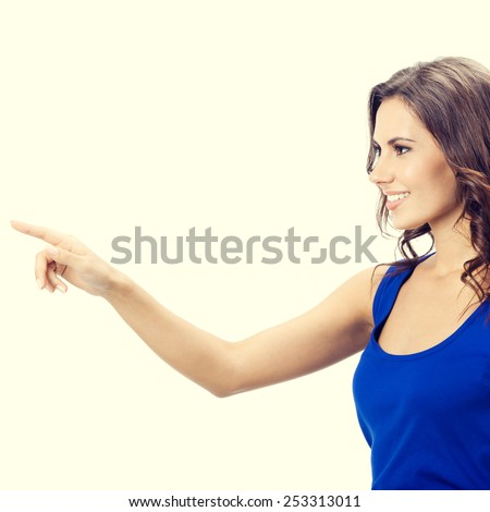 Portrait of cheerful smiling young woman showing copyspace, visual imaginary or something, or pressing virual button  - stock photo