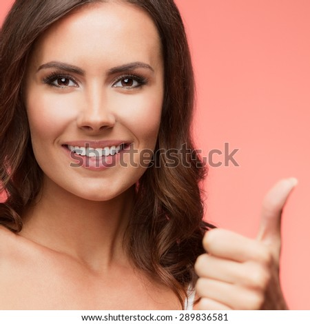 Portrait of cheerful smiling young woman showing thumb up gesture, over light red background