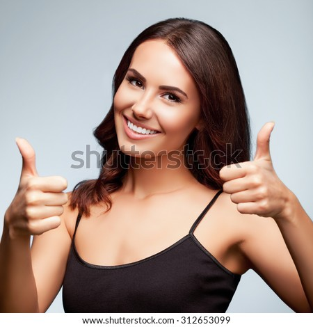 Portrait of cheerful smiling young woman showing thumb up hand sign gesture, over bright grey background, square composition - stock photo