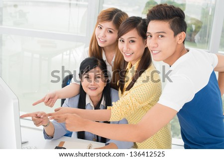 Portrait of cheerful students and their tutor pointing at the computer screen