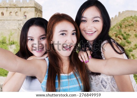 Portrait of cheerful teenage girls using a smartphone to take a selfie on the Great Wall of China - stock photo