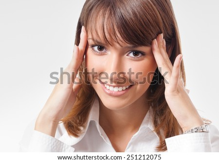 Portrait of cheerful thinking or planning young businesswoman, looking at camera - stock photo