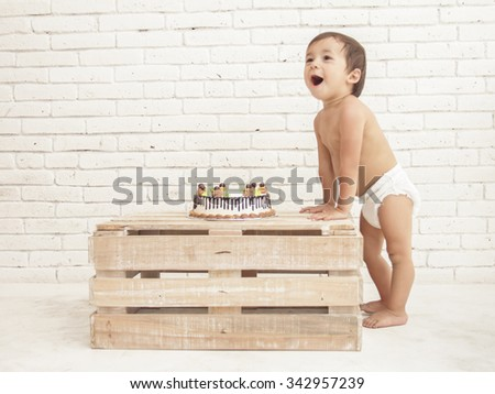 portrait of cheerful toddler and his cake on wooden box with white walls on background - stock photo