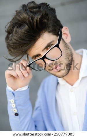 Portrait of cheerful trendy guy with black eyeglasses on