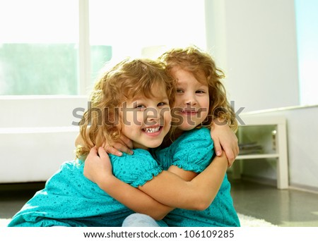 Portrait of cheerful twin sisters hugging and smiling at cam - stock photo