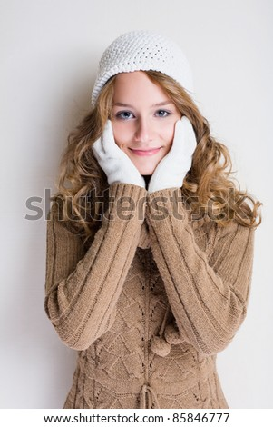 Portrait of cheerful winter fashion girl warming up for the cold season.