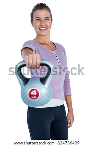 Portrait of cheerful woman exercising with kettlebell against white background - stock photo