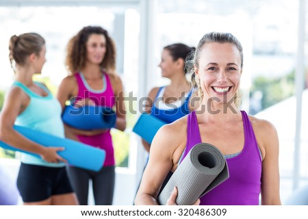 Portrait of cheerful woman holding exercise mat and smiling in fitness studio - stock photo