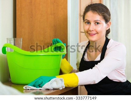 Portrait of cheerful woman in apron and rubber gloves dusting furniture at home - stock photo