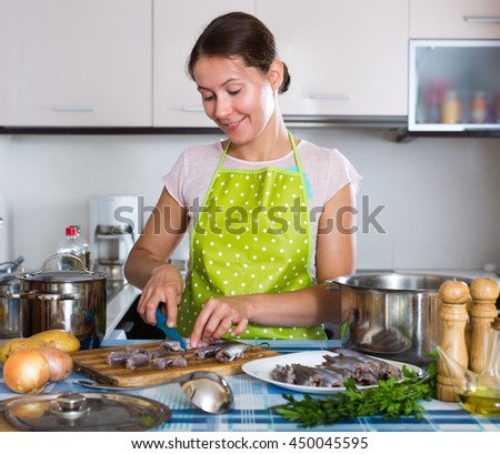 Portrait of cheerful woman in apron preparing small fish in the kitchen - stock photo
