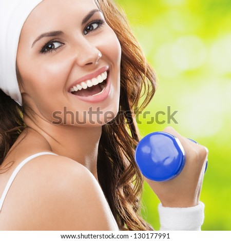 Portrait of cheerful woman in fitness wear exercising with dumbbell, outdoors, with copyspace