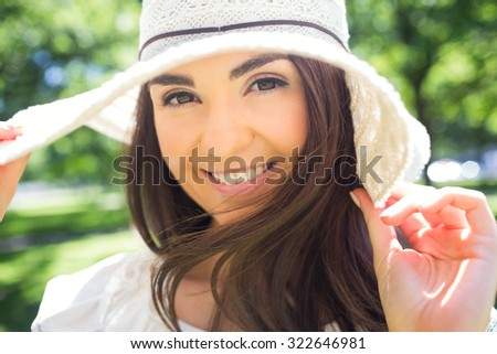 Portrait of cheerful woman in sun hat while standing in park - stock photo