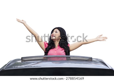 Portrait of cheerful woman out from the sunroof of new car, isolated on white background