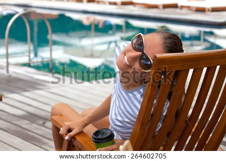 Portrait of cheerful woman, relaxing at the luxury poolside. Girl at travel spa resort pool. Summer luxury vacation. (focus on woman face) - stock photo