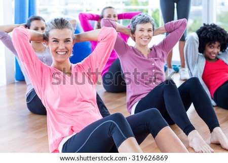 Portrait of cheerful women doing sit ups on hardwood floor in fitness studio - stock photo