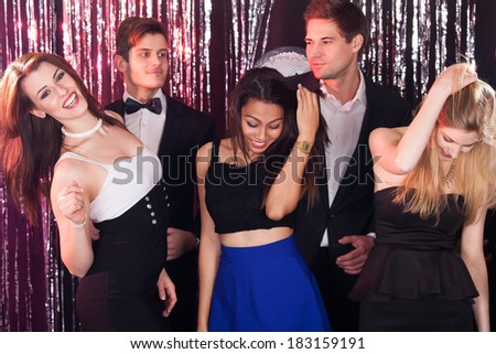 Portrait of cheerful women enjoying party with male friends at nightclub