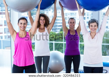 Portrait of cheerful women holding exercise balls with arms raised in fitness studio - stock photo