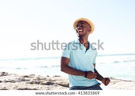 Portrait of cheerful young african man with hat enjoying at the beach on summer day - stock photo
