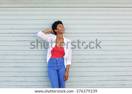 Portrait of cheerful young african woman standing against a wall and looking up at copy space - stock photo