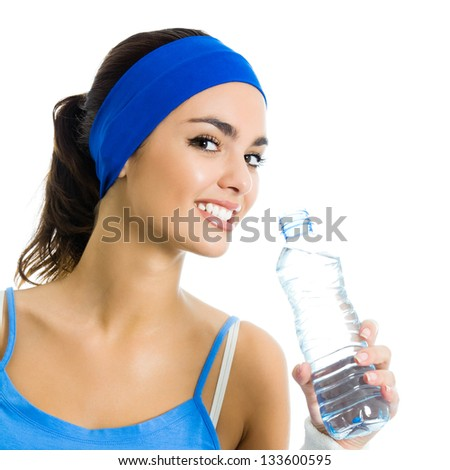 Portrait of cheerful young attractive woman in fitness wear drinking water, isolated over white background - stock photo