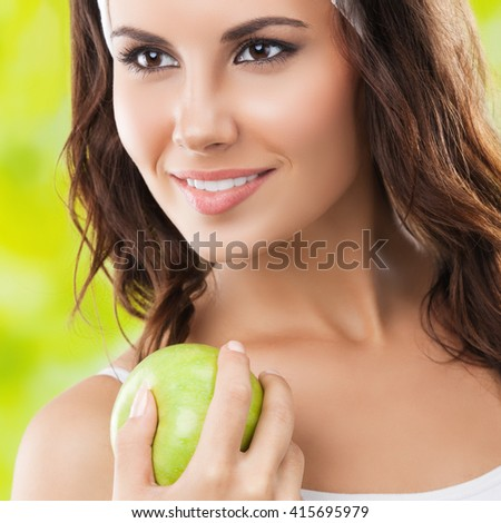 Portrait of cheerful young beautiful brunette woman in fitness wear with apple, outdoors. Healthy lifestyle, beauty and dieting concept. - stock photo