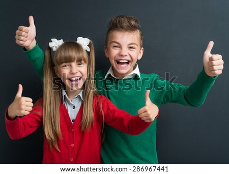 Portrait of cheerful young boy and girl showing thumbs up sign at the black chalkboard in classroom. - stock photo