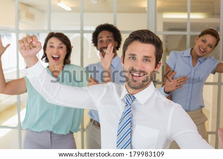 Portrait of cheerful young business colleagues cheering in the office
