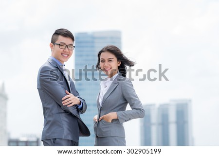 Portrait of cheerful young business people standing outdoors