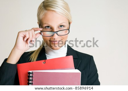 Portrait of cheerful young business woman in glasses holding folders. - stock photo