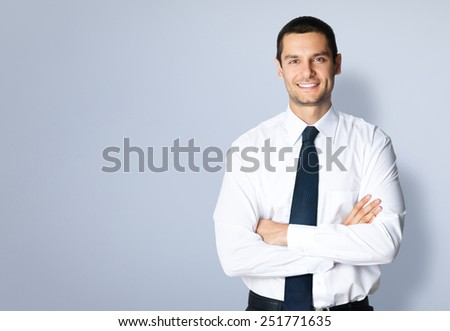 Portrait of cheerful young businessman with crossed arms pose, with blank copyspace area for text or slogan, against grey background - stock photo