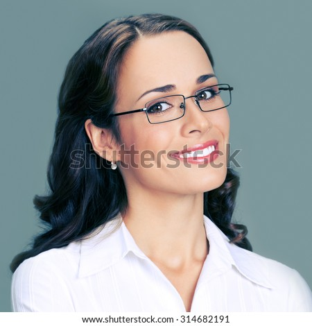 Portrait of cheerful young businesswoman in glasses - stock photo