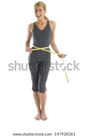 Portrait of cheerful young Caucasian woman holding tape measure around waist against white background - stock photo