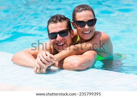 portrait of cheerful young couple in swimming pool - stock photo