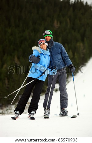 Portrait of cheerful young couple on skis against conifers background - stock photo