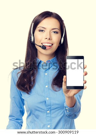 Portrait of cheerful young customer support phone operator showing blank no-name cellphone - stock photo