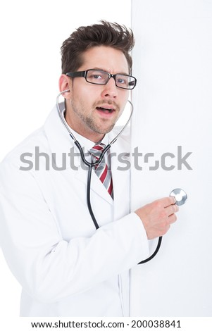 Portrait of cheerful young doctor examining billboard with stethoscope over white background - stock photo