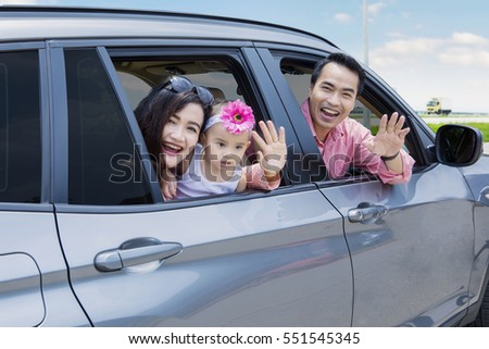 Portrait of cheerful young family looks happy while smiling at the camera and waving hands in the car