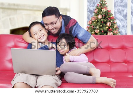 Portrait of cheerful young father and his children watching movie with laptop on sofa, shot with a christmas tree background