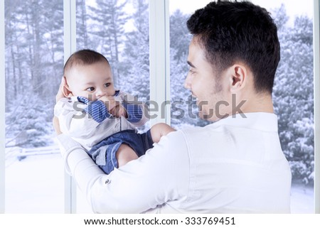 Portrait of cheerful young father holding his adorable male baby at home, shot with winter background on the window - stock photo